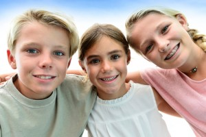 Kids smiling with their braces on.